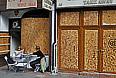 Посетители винного бара в западной части Лондона. Множество магазинов, баров и прочих подобных заведений теперь защищают свои витрины специальными щитами