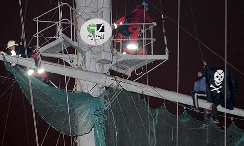 """Молодые люди (справа), вывесившие на крейсере """"Аврора"""" пиратский флаг """"Веселый Роджер"""", на мачте корабля."""