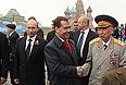 Исполняющий обязанности министра обороны РФ Анатолий Сердюков, президент РФ Владимир Путин и председатель правительства России Дмитрий Медведев во время военного Парада Победы на Красной площади.