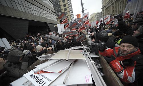 Полицейские требуют граждан освободить проезжую часть. Тем временем, некоторые из оставшихся фотографируются на фоне мусорных баков, в которых сложены портреты депутатов. Полицейские наблюдают за этим с огнетушителями наготове.