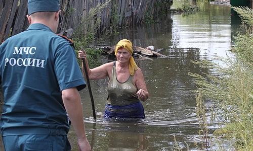 Сотрудник МЧС разговаривает с дачницей, отказавшейся от эвакуации из подтопленного паводковыми водами дома в поселке Уссурийском на Большом Уссурийском острове под Хабаровском.