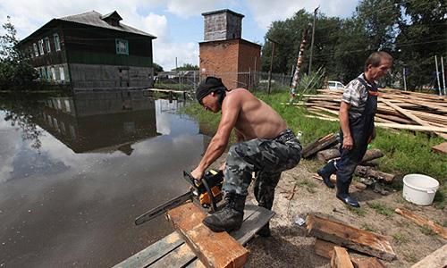 Местные жители строят деревянный мост к подтопленному паводковыми водами Амура дому в поселке Уссурийском на Большом Уссурийском острове под Хабаровском.