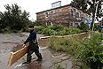 Рабочие строят деревянные мостки к домам, подтопленным паводковыми водами. Уровень воды в реке Амур у Хабаровска в воскресенье достиг исторического максимума в 642 сантиметра.
