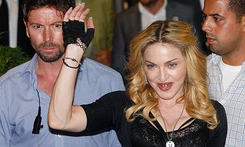 """В Риме певица Мадонна поприсутствовала на открытии фитнес-центра """"Hard Candy"""" и улыбнулась."""