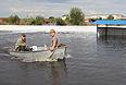 Жители затопленного поселка Владимировка, расположенного в трех километрах от города Благовещенск Амурской области, плывут на лодке по улице.