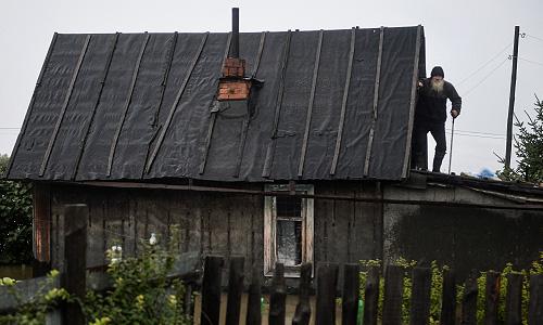 Житель поселка Уссурийский на крыше своего затопленного дома.