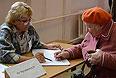 Женщина получает избирательный бюллетень на одном из избирательных участков на выборах мэра Москвы.
