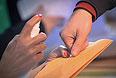 Сотрудница избирательной комиссии ставит отметку о голосовании на руке избирателя.