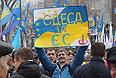 """Участник митинга """"За европейскую Украину"""" за подписание соглашения об ассоциации с Евросоюзом с плакатом """"Люби Украину или иди вон!"""" держит плакат """"Одесса за ЕС"""" на Европейской площади в Киеве."""