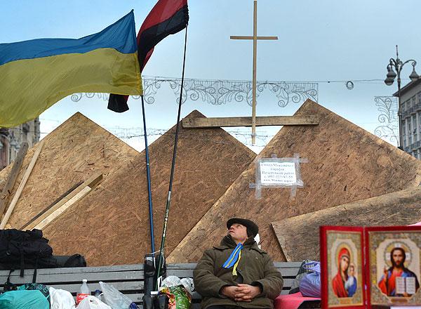 Участник акций сторонников вступления Украины в Евросоюз греются ночью у костра на площади Независимости в Киеве.