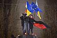 Участники акции в поддержку евроинтеграции Украины стоят на постаменте памятника Ленину, снесенного ими на Бессарабской площади в центре Киева.