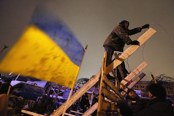 """Первую ночь после попытки штурма правоохранителями """"евромайдана"""" митингующие на майдане Независимости провели, сооружая новые и укрепляя ранее возведенные баррикады, а также принимая пополнение от """"майдановцев"""" из других областей Украины"""