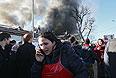 """Продавщица говорит по телефону во время пожара на центральном рынке """"Беркат"""" в Грозном."""