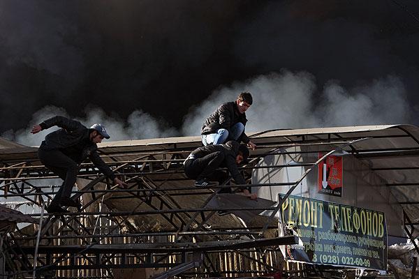 """Молодые люди снимают пластиковое покрытие с павильона во время пожара на центральном рынке """"Беркат"""" в Грозном."""