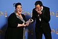 """Участники церемонии Мелисса МакКарти и Джимми Фэллон разыгрывают сценку, в которой Фэллон принимает клатч МакКарти за статуэтку """"Золотой глобус""""."""