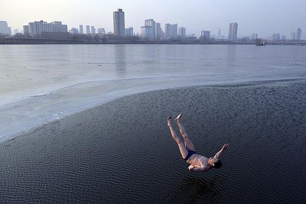 Китайский пенсионер семидесятичетырех лет ныряет в замерзшую реку.