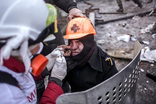 """Сторонники оппозиции оказывают медицинскую помощь мужчине, пострадавшему во время столкновений с сотрудниками правоохранительных органов у стадиона """"Динамо"""" в Киеве."""