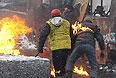 Двое протестующих прячутся за сгоревшим автобусом, на одном из них загорелась куртка.