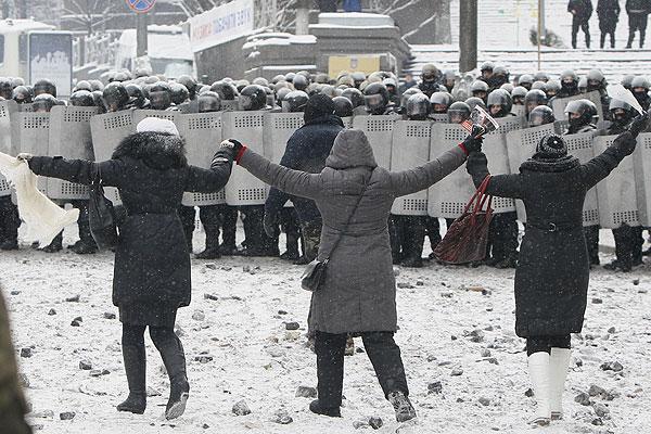Киевские женщины взявшись за руки идут навстречу сотрудникам правоохранительных органов Украины.
