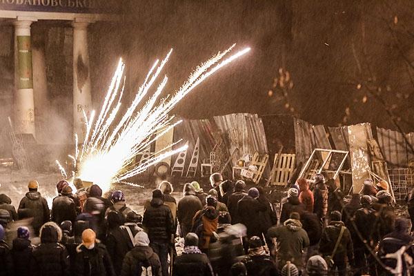 Митингующие запускают петарды на улице Грушевского в Киеве.