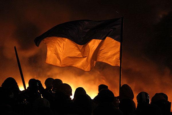 Украинский флаг развевается над головами протестующих.