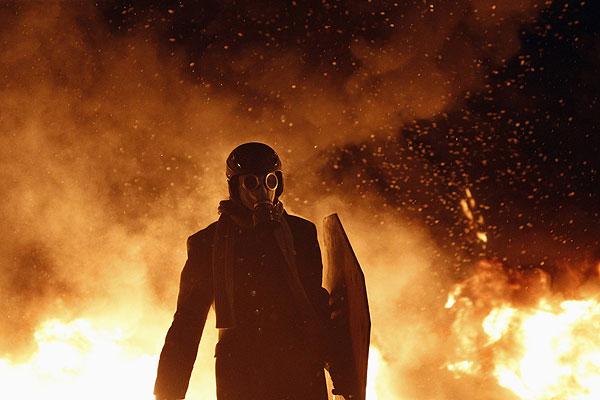 Участник киевского протеста в противогазе и со щитом продвигается в клубах дыма и огня в районе улицы Грушевского.