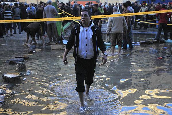 Мужчина бредет по щиколотку в воде на месте взрыва в Каире.
