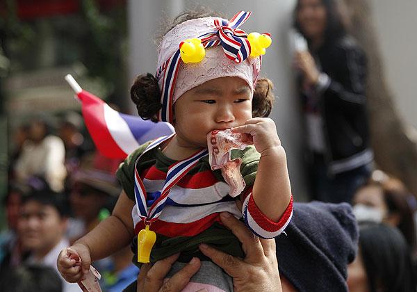 Маленькая девочка сжимает в руках деньги, чтобы передать их на нужды оппозиции Таиланда.
