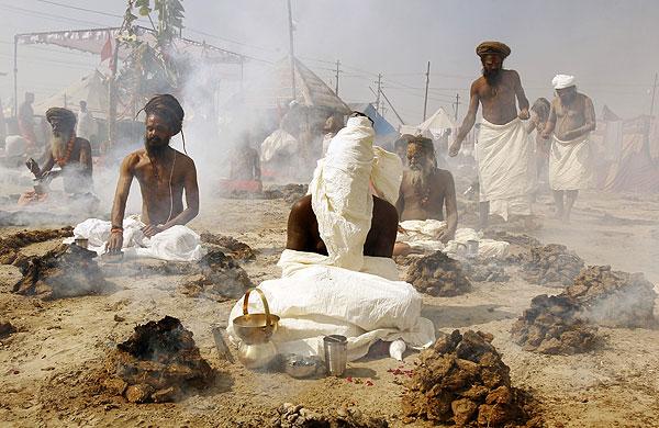 Индийские аскеты молятся среди дымящихся куч коровьего навоза.