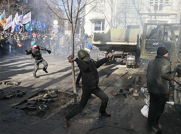 Манифестанты бросают камни в сторону милицейского оцепления.