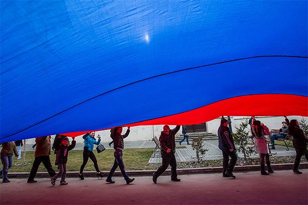 Члены пророссийских организаций несут гигантский флаг РФ.