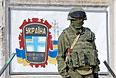 Военнослужащий стоит на страже возле украинской военной базы в селе Перевальное.