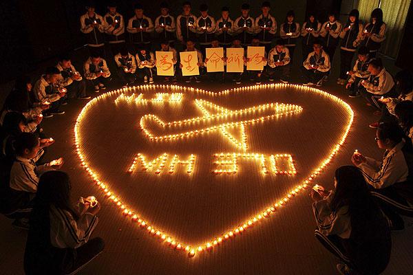 Школьники зажигают свечи в память о пропавших пассажирах рейса MH370.