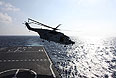 """Вертолет, принимающий участие в спасательной операции, поднимается с платформы боевого корабля """"Джинганшан""""."""