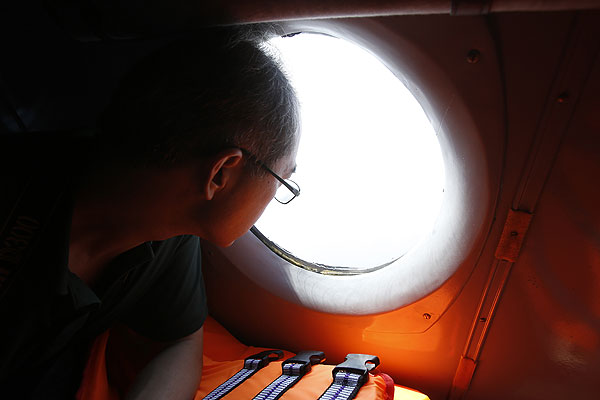 Китайский журналист выглядывает в иллюминатор борта вьетнамских ВВС во время поисковой операции.