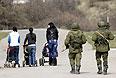 Женщины с колясками на прогулке. Позади идут военные.