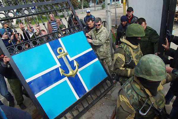 Представители сил самообороны Крыма и военнослужащие штурмуют штаб Военно-морских сил Украины.