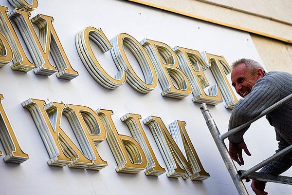 """Рабочие устанавливают надпись """"Государственный совет"""" вместо демонтированной вывески с названием """"Верховная рада"""" на здание парламента Крыма."""