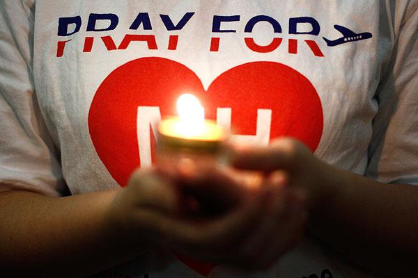 Горящая свеча во время молитвы за пассажиров малайзийского Boeing-777.