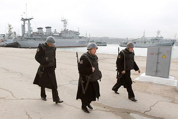 """Российские моряки в порту Севастополя. На заднем плане украинский военный корабль """"Славутич""""."""