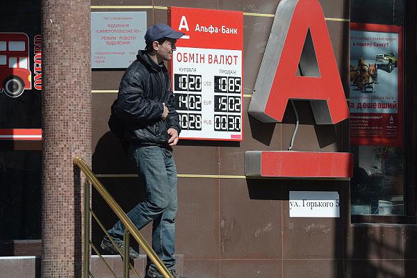 """Мужчина выходит из отделения """"Альфа-Банка"""" в Симферополе."""
