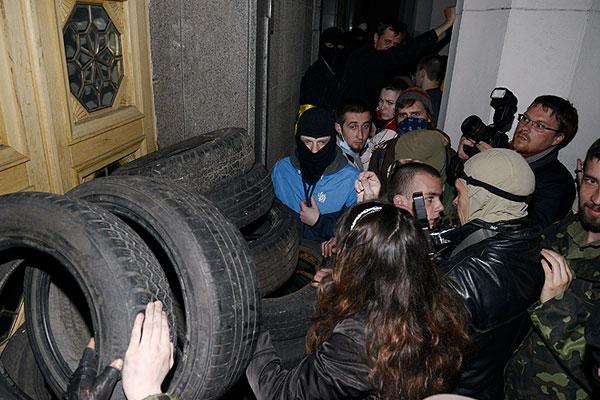 """Активисты """"Правого сектора"""" и фотографы в толпе перед входом в здание Верховной рады, заблокированным автомобильными шинами."""