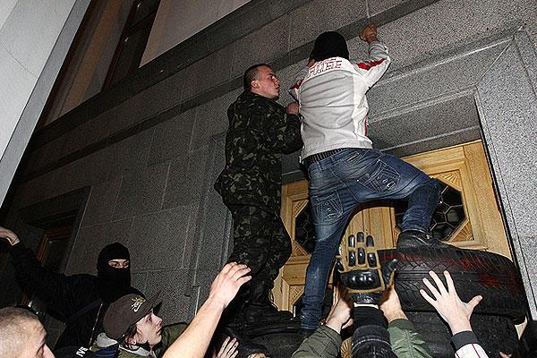 """Активисты """"Правого сектора"""" пытаются забраться на стену здания Верховной рады в Киеве."""