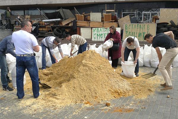 Митингующие фасуют мешки с песком для строительства баррикад вокруг здания областной госадминистрации, захваченного сторонниками федерализации в Донецке.