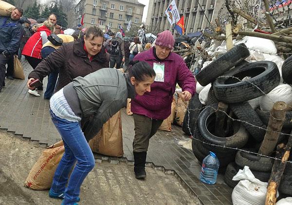 Сторонники федерализации Украины несут мешки с песком для строительства баррикад вокруг здания областной госадминистрации в Донецке.