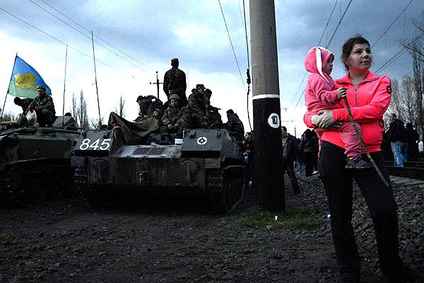 Жительница Краматорска с маленьким ребенком на руках стоит рядом с украинскими танками.