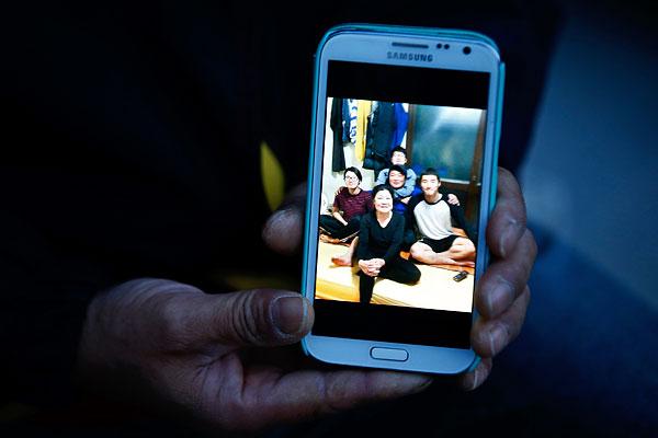 Мужчина показывает семейную фотографию со своим младшим сыном, который числится пропавшим без вести.
