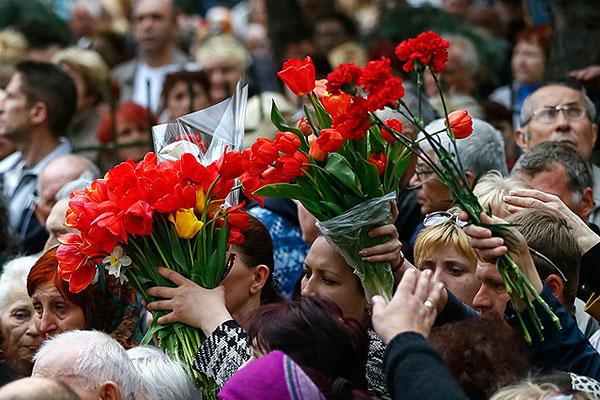 Женщины несут цветы во время похорон трех ополченцев, погибших в перестрелке 20 апреля в Славянске.