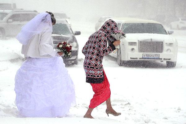 Невеста идет по улице во время сильного снегопада в Челябинске.
