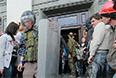 Представители самообороны выходят из здания областной администрации в Луганске, взятого под контроль сторонниками федерализации.